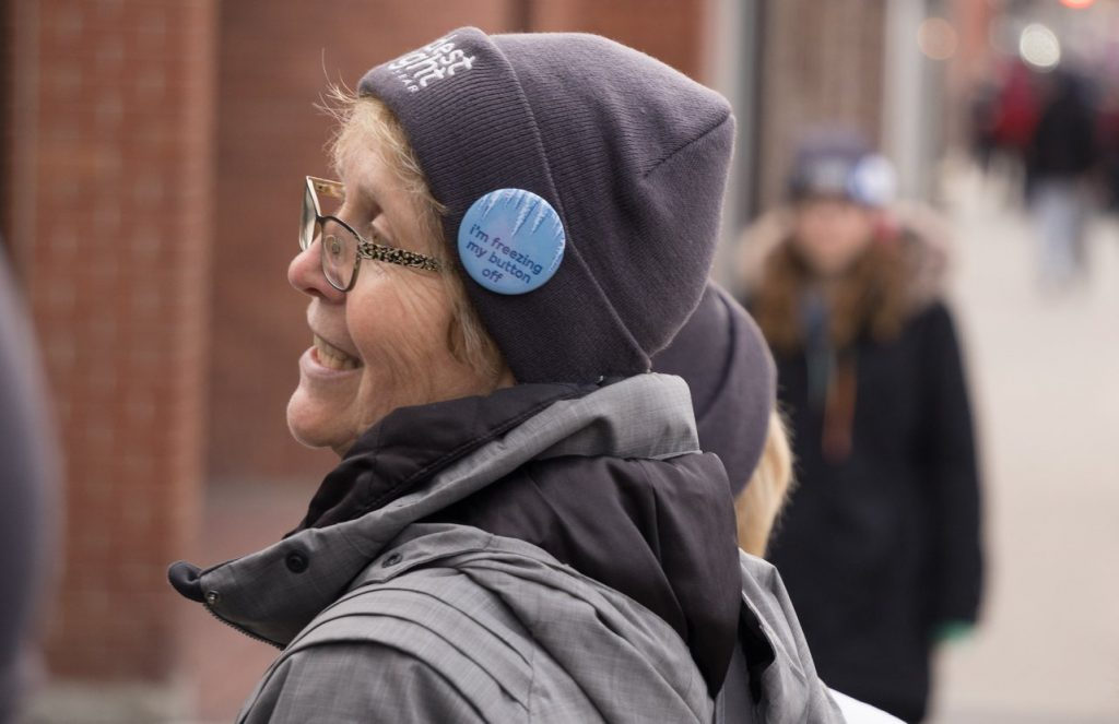 """Woman wearing grey Coldest Night toque and """"I'm freezing my button off"""" button"""
