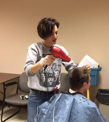 A woman blowdries a man's hair