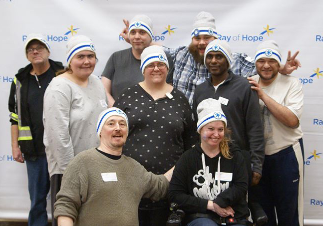 A group of volunteers wearing Coldest Night toques stand in front of the Ray of Hope backgrop