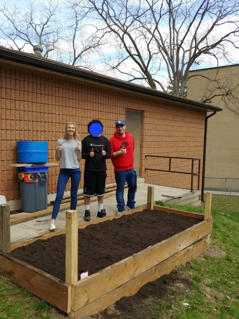 woman and two men stand next to a raised garden bed