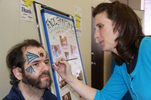 A woman applies face paint to Rick's face