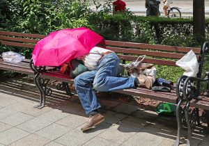 Homeless man is sleeping on a bench in the city