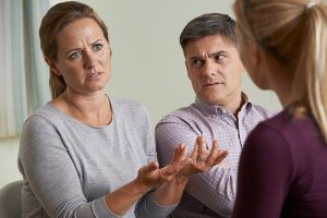 An upset-looking woman getsrures while speaking to a female counsellor while a man looks on