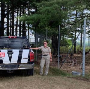 Young woman in khaki uniform stands next to a zebra-striped truck