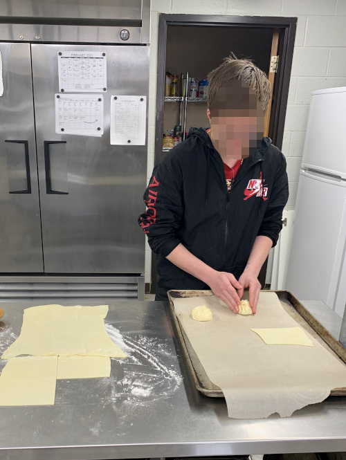 Young man making pastry in a kitchen