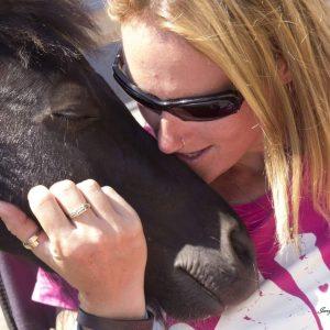 Closeup of Julie cuddling a pony