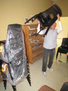 Jon lifts a black chair over his head