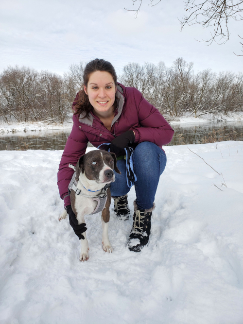 Kate kneels next to a brown and white dog in a snowy field