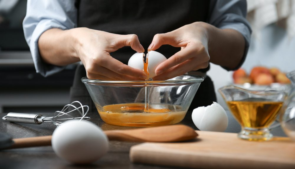 Closeup of a woman's hands as she breaks and egg into a glass bowl