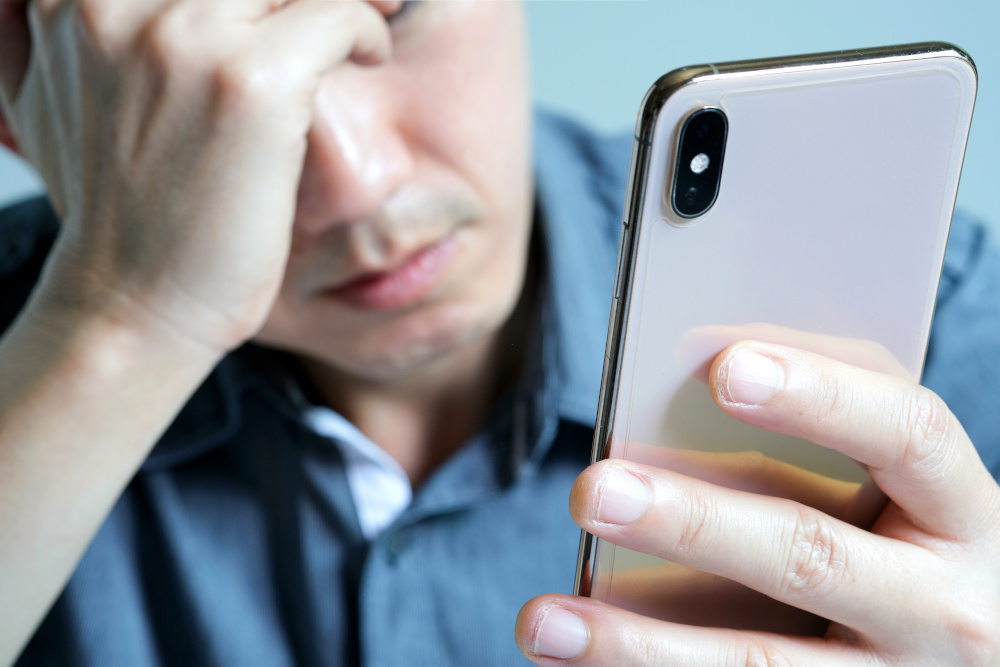 A distressed young man rubs his eyes while holding his phone